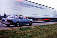 /images/133/1998-11-lancing-tempo-semi.jpg - #00169: my blue 1986 Ford Tempo … them trucks go faaast … Nov 1998 -- Lancing, Michigan