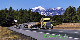 /images/133/2003-08-flagstaff-peaks3-pano.jpg - #01279: cars and yellow Semi Truck leaving Flagstaff and San Francisco Peaks behind … August 2003 -- Humphreys Peak, Flagstaff, Arizona
