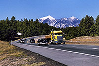 /images/133/2003-08-flagstaff-peaks3.jpg - #01298: cars and yellow Semi Truck leaving Flagstaff and San Francisco Peaks behind … August 2003 -- Humphreys Peak, Flagstaff, Arizona